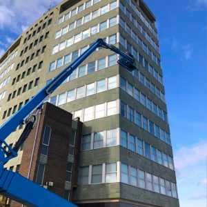 Food Sector Construction employee on a cherry picker performing building maintenance work on Ross House, Headquarters of Youngs Seafood, Grimsby